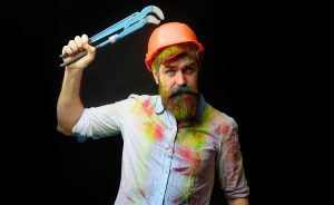 Bearded plumber holding a monkey wrench