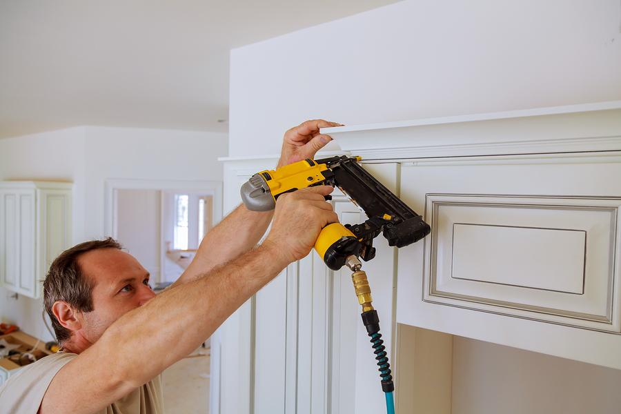 Handyman using gauge nails on a baseboard